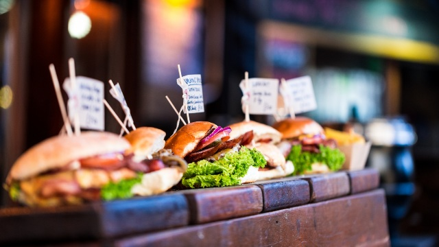 Burgers lined up on a wooden counter.