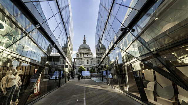 St Paul's Cathedral, in the background, is reflected in the glass walls on both sides of a narrow alleyway at One New Change.