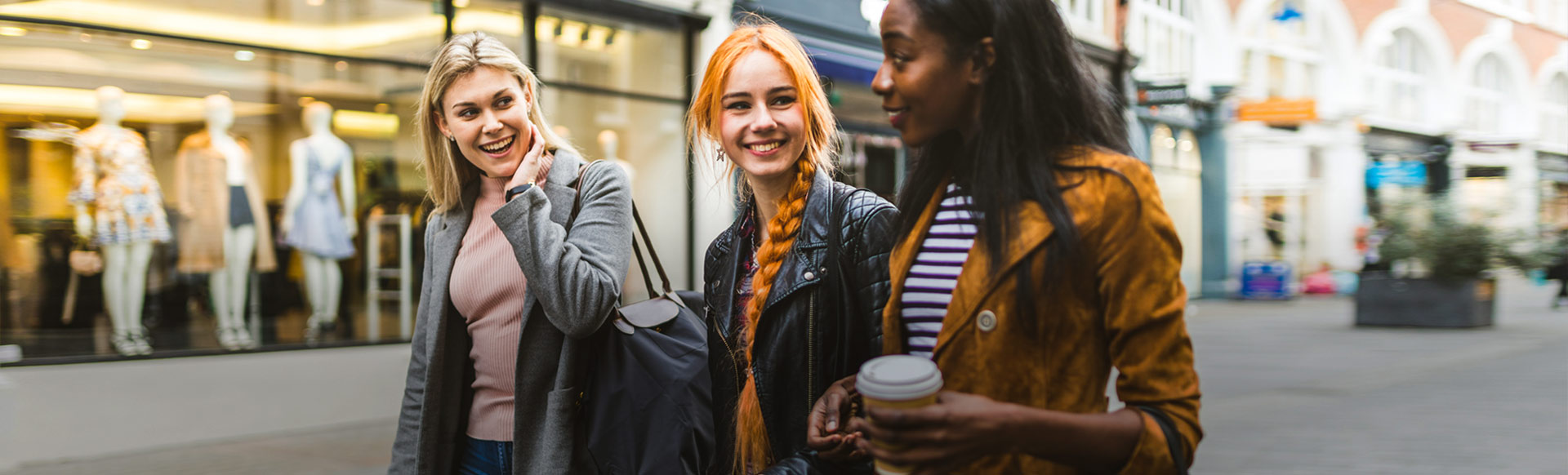 Three young women chatting on a shopping street