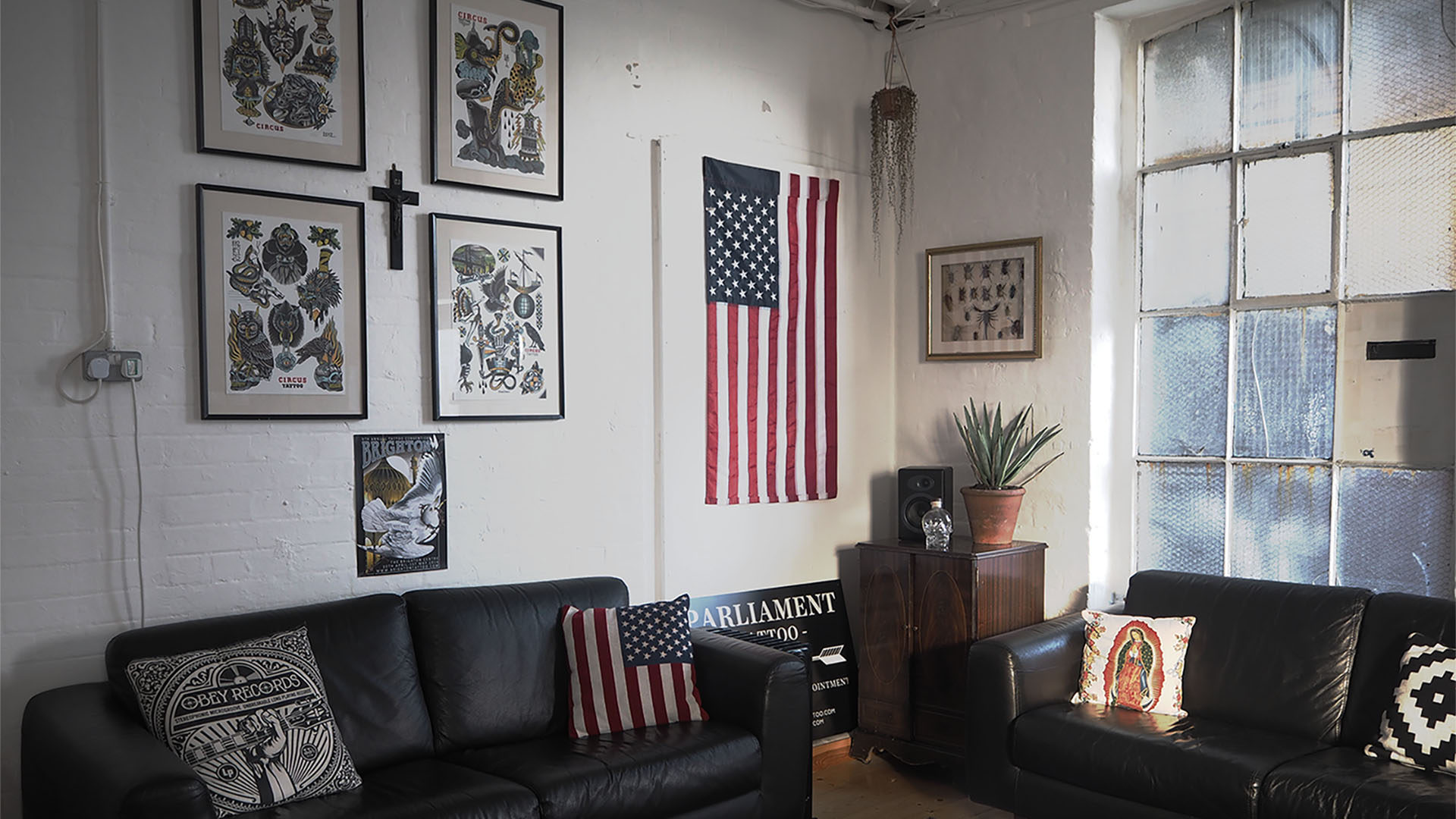 Reception room of Parliament tattoo featuring two leather sofas, drawings of tattoos and an American flag hanging on a white wall.