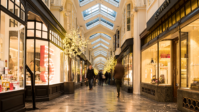 Looking along Burlington Arcade, with little shops and Christmas decorations either side and people further along the arcade.