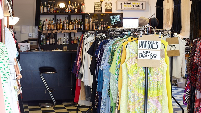 Rails of retro dresses in front of a bar at Paper Dress Vintage clothing shop