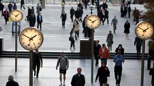 Clocks and people walking in London's Canary Wharf.