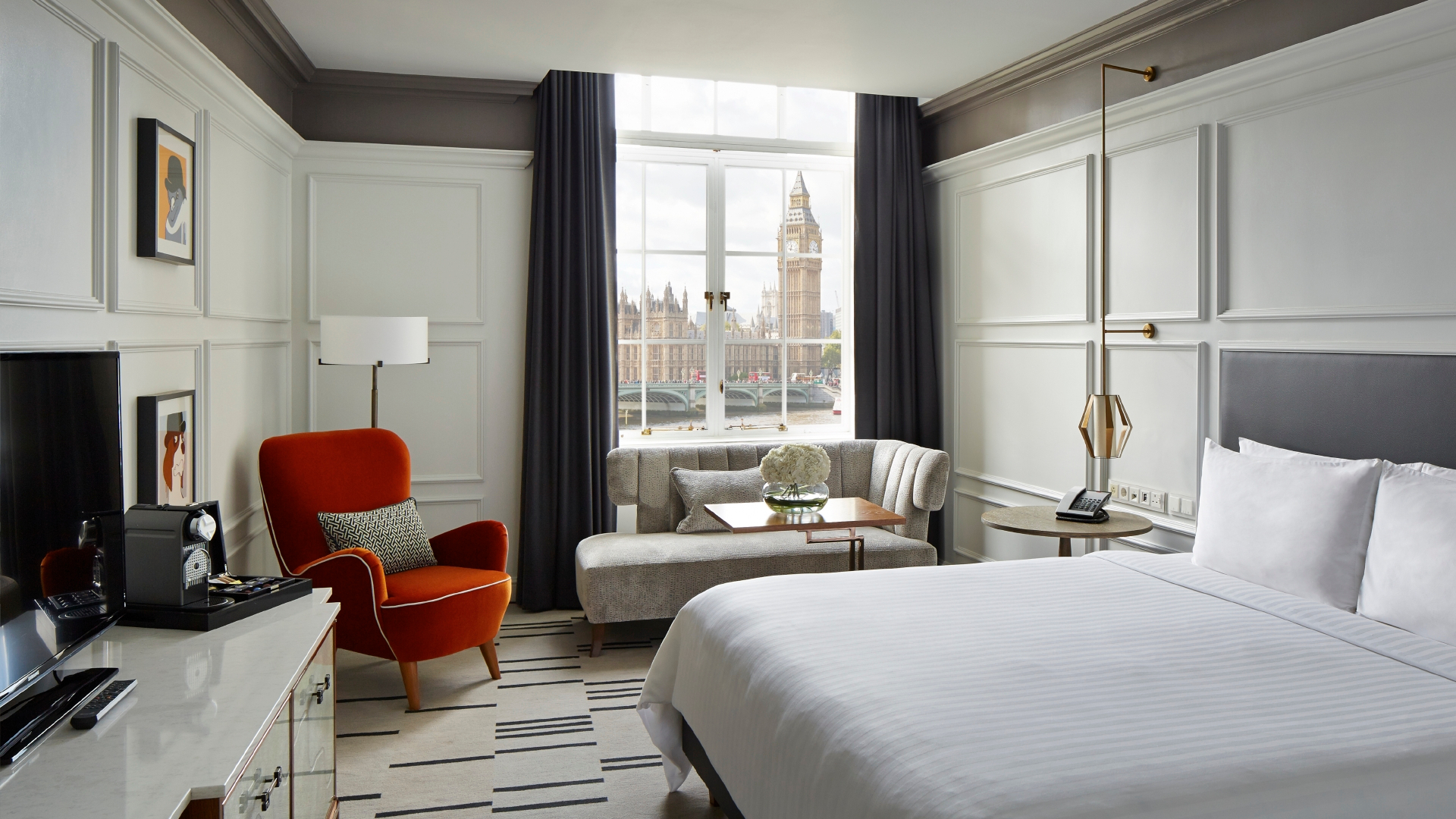 Luxury hotel room with white bedding, red chair, black curtains and view of Big Ben and Parliament.