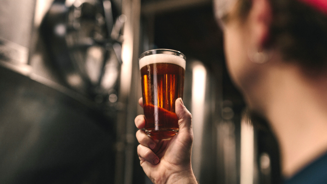 A man is holding a freshly-poured pint in the light of a brew house.