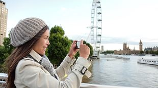 A lady, wearing a beanie hat and a coat, takes a photograph with her phone, with the London Eye in the background.