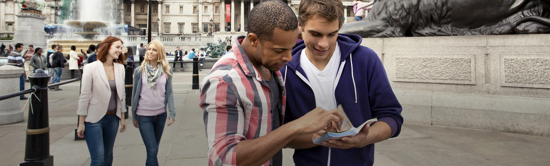 Two men looking at a guidebook in Trafalgar Square. © London and Partners/Pawel Libera