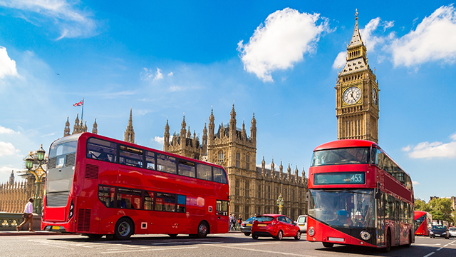 Two red London buses pass in front of Big Ben and the Houses of Parliament on a sunny day.