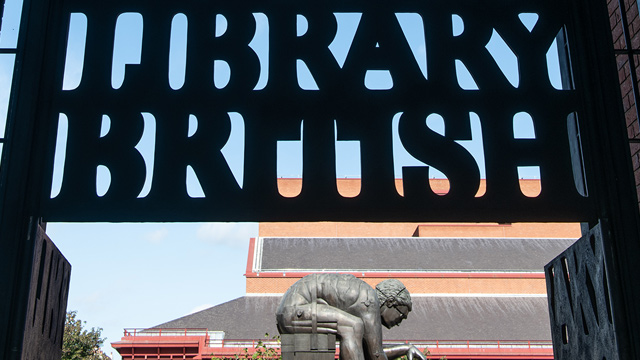 Black sign of the British Library with a sculpture in the background.
