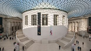 Looking down on The Great Court from high, with a light blue glass roof and central circular room, surrounded by a covered courtyard with people walking around.