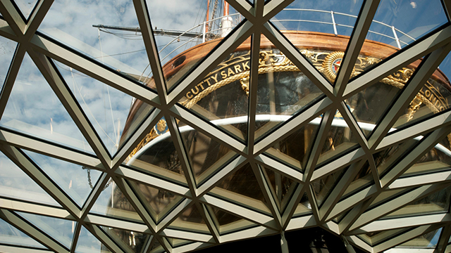 Looking up from beneath the hull of Cutty Sark - with the crisscross pattern of the glass ceiling above and the stern of the black and gold ship beyond