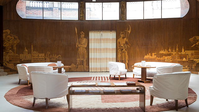 The entrance hall of Eltham Palace, with art-deco wood panelling featuring gold-coloured designs of soldiers and landscapes, white chars and a circular pink rug.