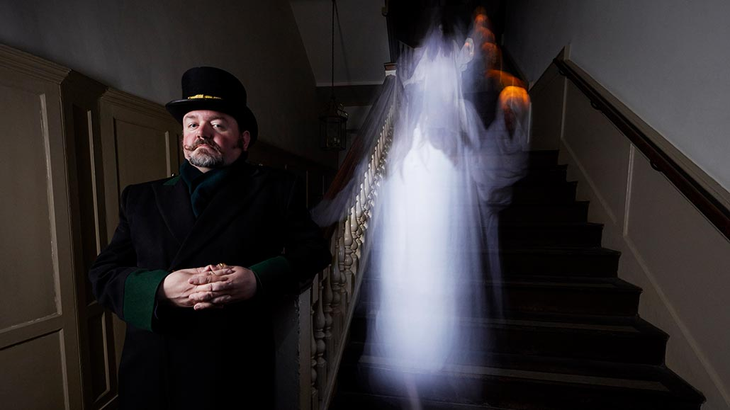 A warden looks ahead as a ghostly apparition appears on the stairs behind him, at Hampton Court Palace.