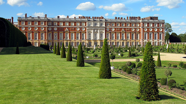 A row of trees and a neatly kept lawn in the foreground leads towards the red brick facade of Hampton Court Palace in the background.