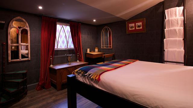 A Harry Potter-themed room at Georgian House Hotel, complete with red-velvet curtains, white sheets and dark wooden floor.