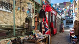 London's Camden Passage, featuring a shop selling vintage clothes, books and other secondhand goods.