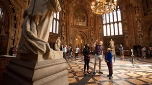 A man, woman and child look up at the ceiling of the Houses of Parliament during an audio tour.