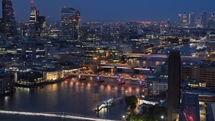 London bridges are lit up along the Thames at night with the skyline.