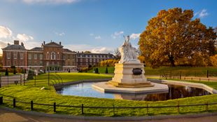 Queen Victoria statue in Kensington Gardens, with tree with autumn leaves, and Kensington Palace in the background