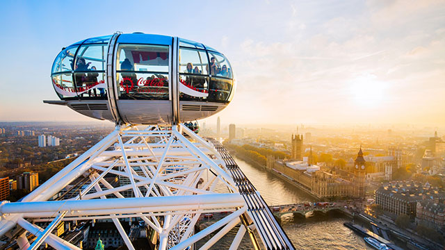 People in a London Eye pod admiring the views of London, with the river Thames and Houses of Parliament below