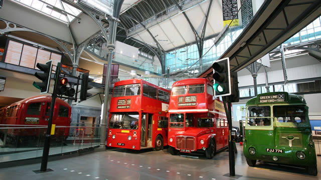 Two red London buses and one green bus, housed within a large room at the London Transport Museum.
