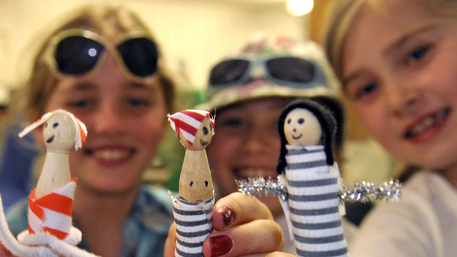 Three kids holding up sailor figures, smiling.