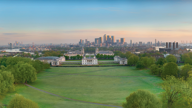 View from above of Greenwich Park, Royal Museums Greenwich, the River Thames and Canary Wharf in the distance.