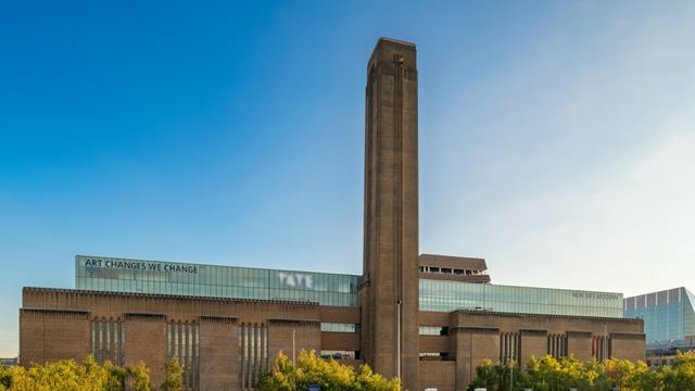 The magnificent chimney of the Tate Modern building against a blue sky.