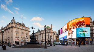 A wide-angle view of Piccadilly Circus on a bright day, with the statue of Eros in the foreground and the famous wall of LED lights illuminated on the right