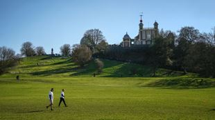 Two men walking in front of Greenwich Hill and Royal Observatory