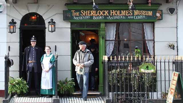 """A man and lady stand to the left of the doorway, dressed in period clothing, while a man walks out of the museum. The front of the museum shows black railings and a green sign above with the wording """"The Sherlock Holmes Museum"""" in yellow."""