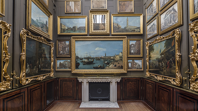 A small room, whose walls are covered in paintings in gold-coloured frames. with wood panelling on the lower walls and a small fireplace.