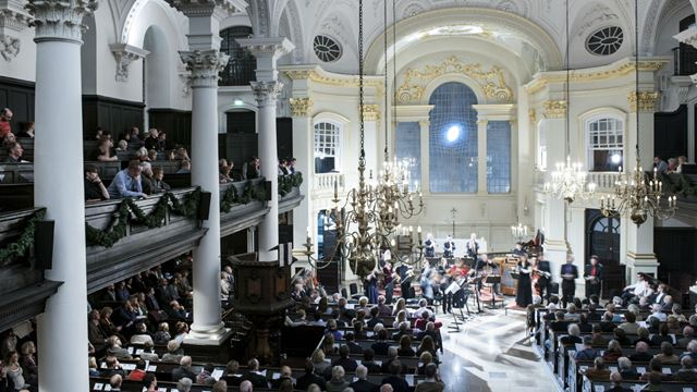 A photo of a crowd in the St Martin-in-the-Fields Church in the evening, attending a ceremony.