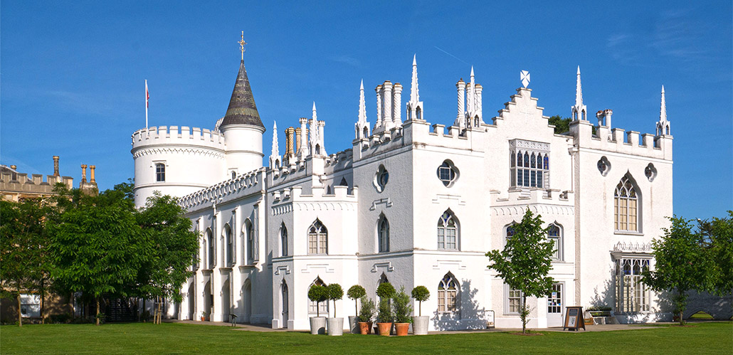 Strawberry Hill House, a white turreted castle, sits upon a grassy hill in front of a blue sky.