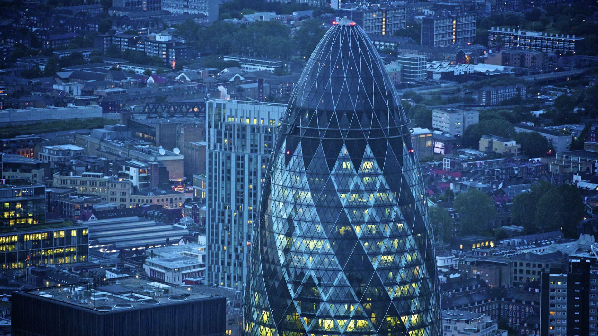 An aerial shot of The Gherkin and the City of London lit up at night. © petewebb.com/London and Partners
