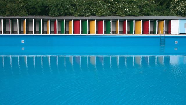 Looking across the pool at the colourful yellow, green and red doors of Tooting Bec Lido.