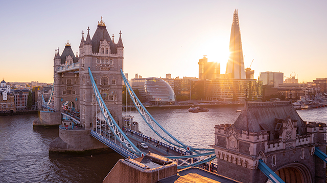 A panoramic view of Tower Bridge and the Thames at sunset, with City Hall and The Shard in the background.