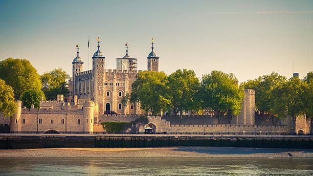 Лондонский Тауэр в сумерках в ясный день, сделанный из-за Темзы.