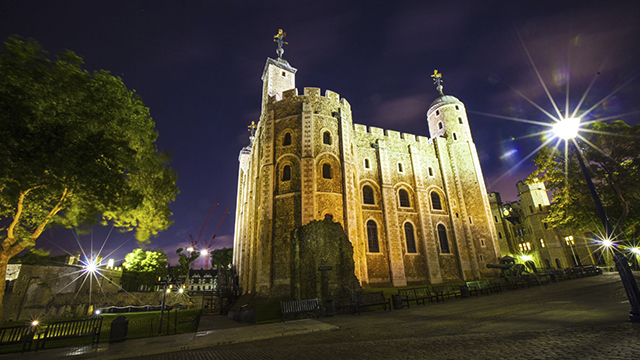The Tower of London, illuminated in a yellow light, at night. A dimly lit tree on the left, lamp post on the right and a purplish dark sky create a spooky feel.