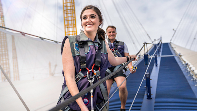 A woman and man walk down the side of The O2, hanging onto a rope and wearing harnesses, during the Up at The O2 experience.
