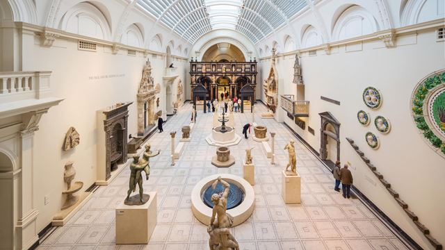 A vast light-filled white hall at Victoria and Albert Museum, featuring  sculptures and statues on pedestals, artefacts on walls and a curved, glass roof.