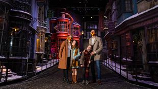 A family of four looking up at the festive features of Hogwarts in the Snow at Warner Bros. Studio Tour London – The Making of Harry Potter.