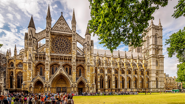 A wide-angle shot of Westminster Abbey on a sunny day, taken from across Parliament Square, with a crowd in the foreground.