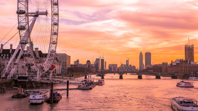 The London Eye at sunset facing the river Thames and the Houses of Parliament