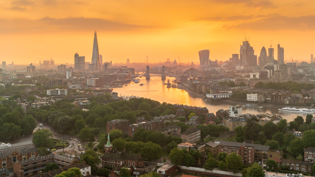 London skyline and river side while the sunset turns the sky orange.