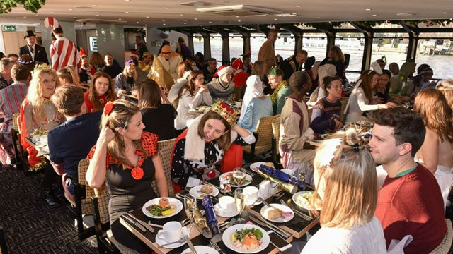 A crowd of people wearing festive costumes enjoying a Christmas Day lunch aboard a cruise.