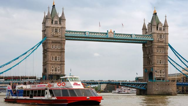City Cruises boat cruising past Tower Bridge on the river Thames.