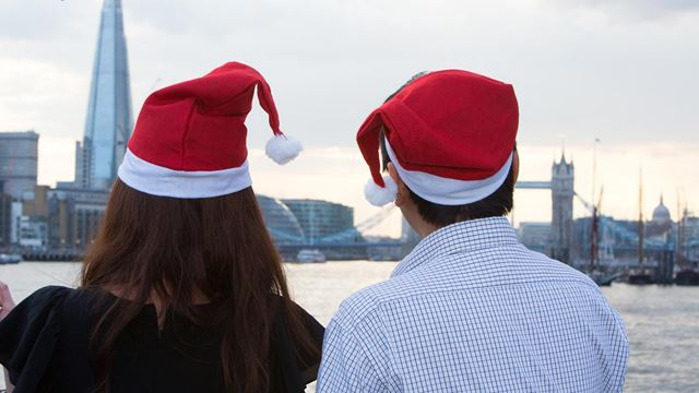Two people in red Santa hats gaze out at the river Thames, the Shard and Tower Bridge from aboard one of City Cruises' boats.