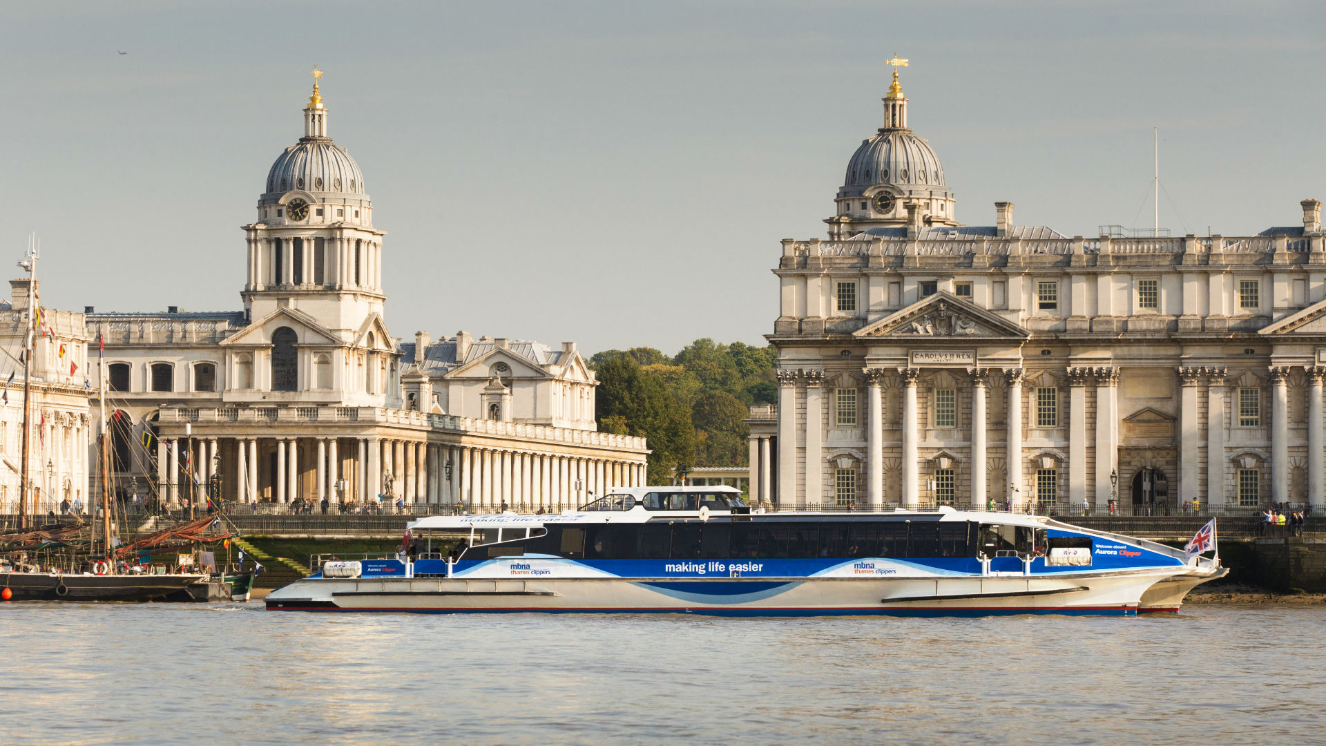 MBNA Thames Clippers on the Thames, against a backdrop of Old Royal Naval College, Greenwich. Image courtesy of Visit Greenwich.