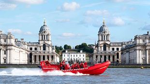 The red Thames Rockets speedboat, complete with passengers dressed in red life jackets, speeds along the Thames  on a sunny day, with the twin domes of Greenwich's Royal Naval College in the background.